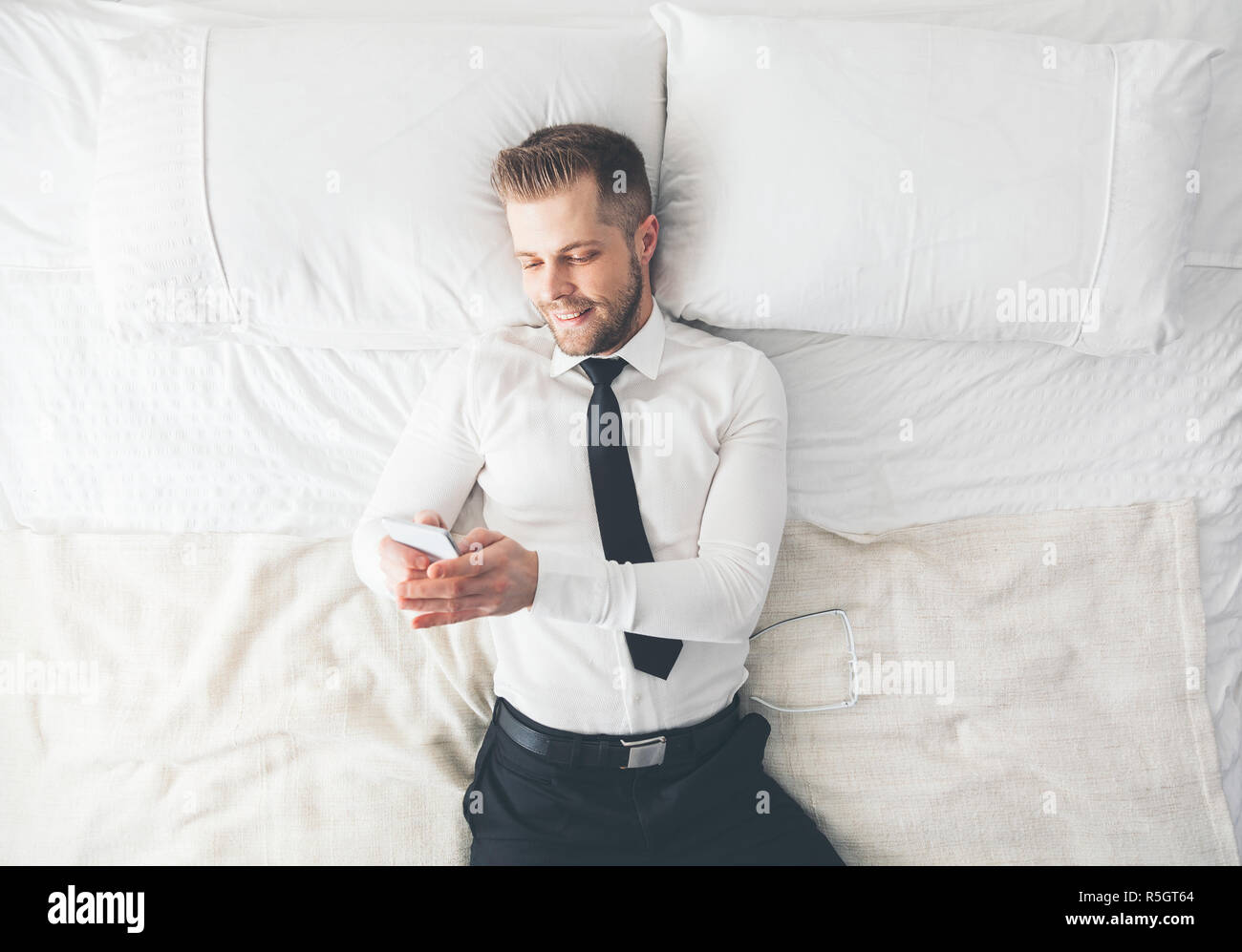 Top view. Handsome businessman lying on bed texting from his smartphone - Stock Image