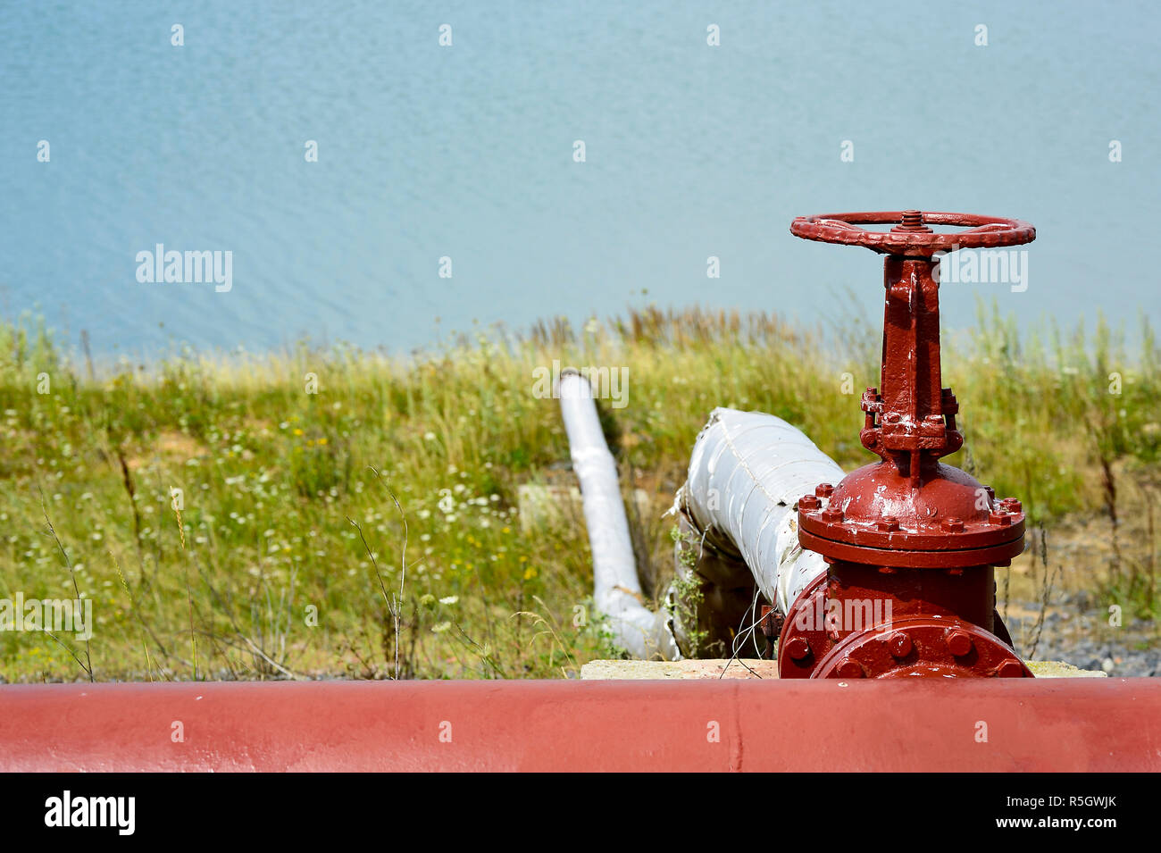 The valve from the pipeline against the background of the factory and an artificial lake - Stock Image