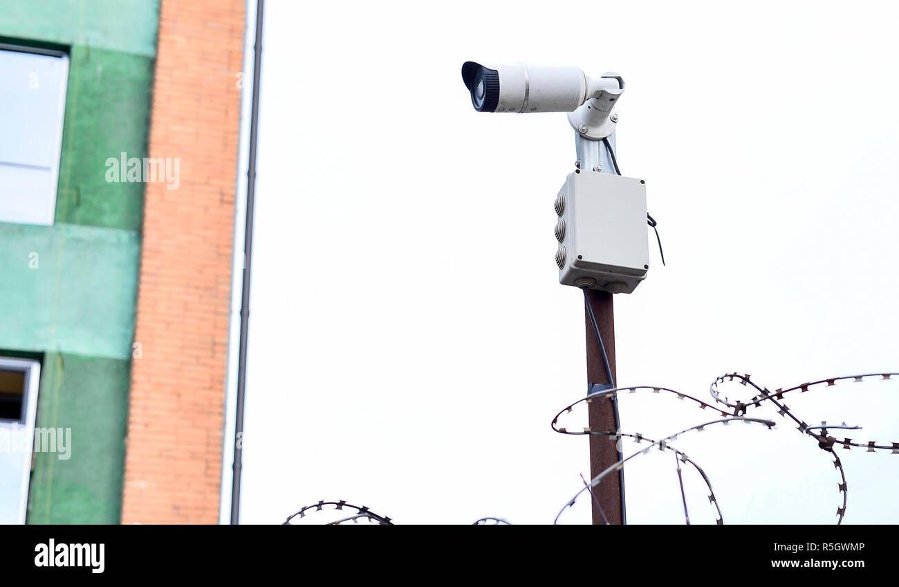 Camera video surveillance on the building background mounted on a brick wall, fenced with barbed wire - Stock Image