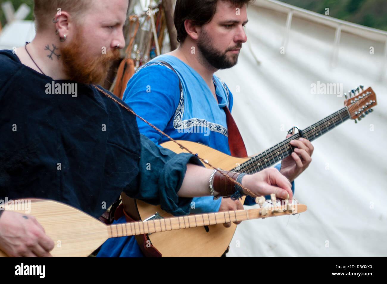 Two viking re-enactors playing stringed musical instruments at Gudvangen viking market, Norway - Stock Image