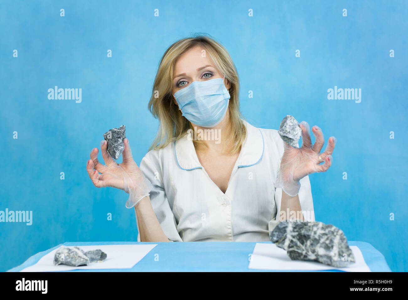 A woman lab worker examines stones for anilization, the content of harmful asbestos. Stock Photo