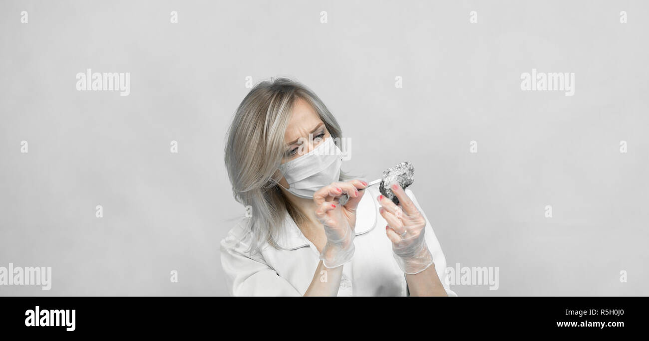 A woman lab worker examines the stones with tweezers takes the fibers of harmful asbestos. Stock Photo