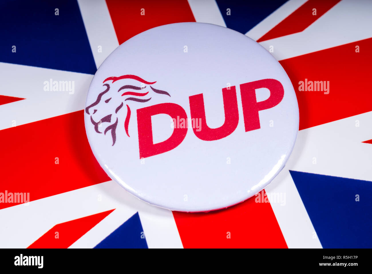 London, UK - November 15th 2018: A Democratic Unionist Party pin badge, pictured over the UK flag. - Stock Image