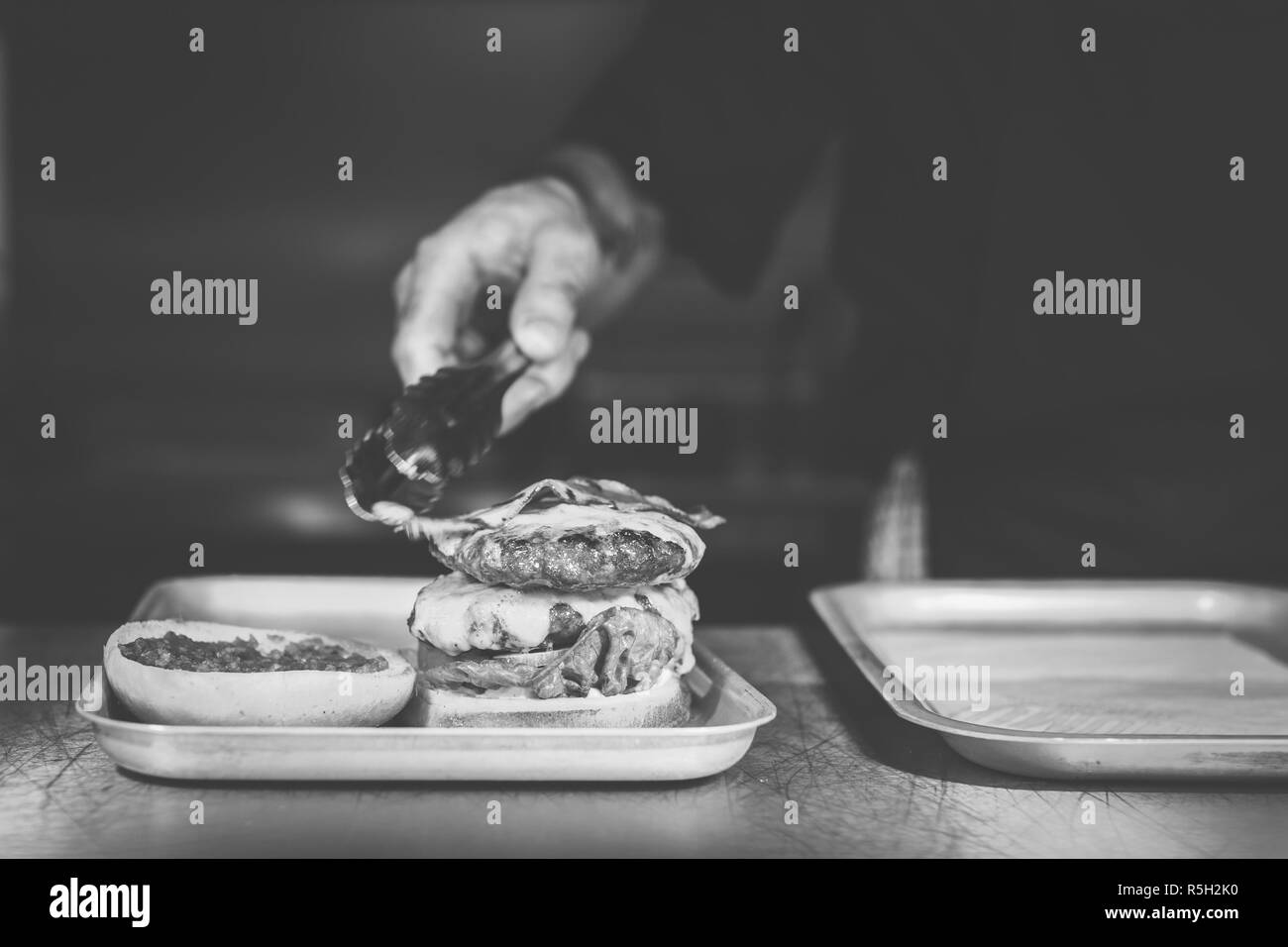 Burger being topped with bacon in black and white - Stock Image