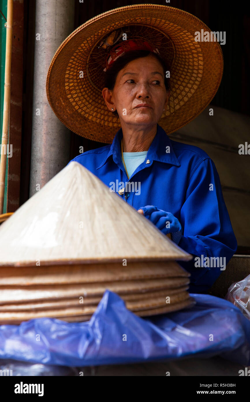 Older woman selling hats in the market of Damnoen Saduak, sitting watching and waiting for the possible approach of some tourist to be able to sell ty - Stock Image