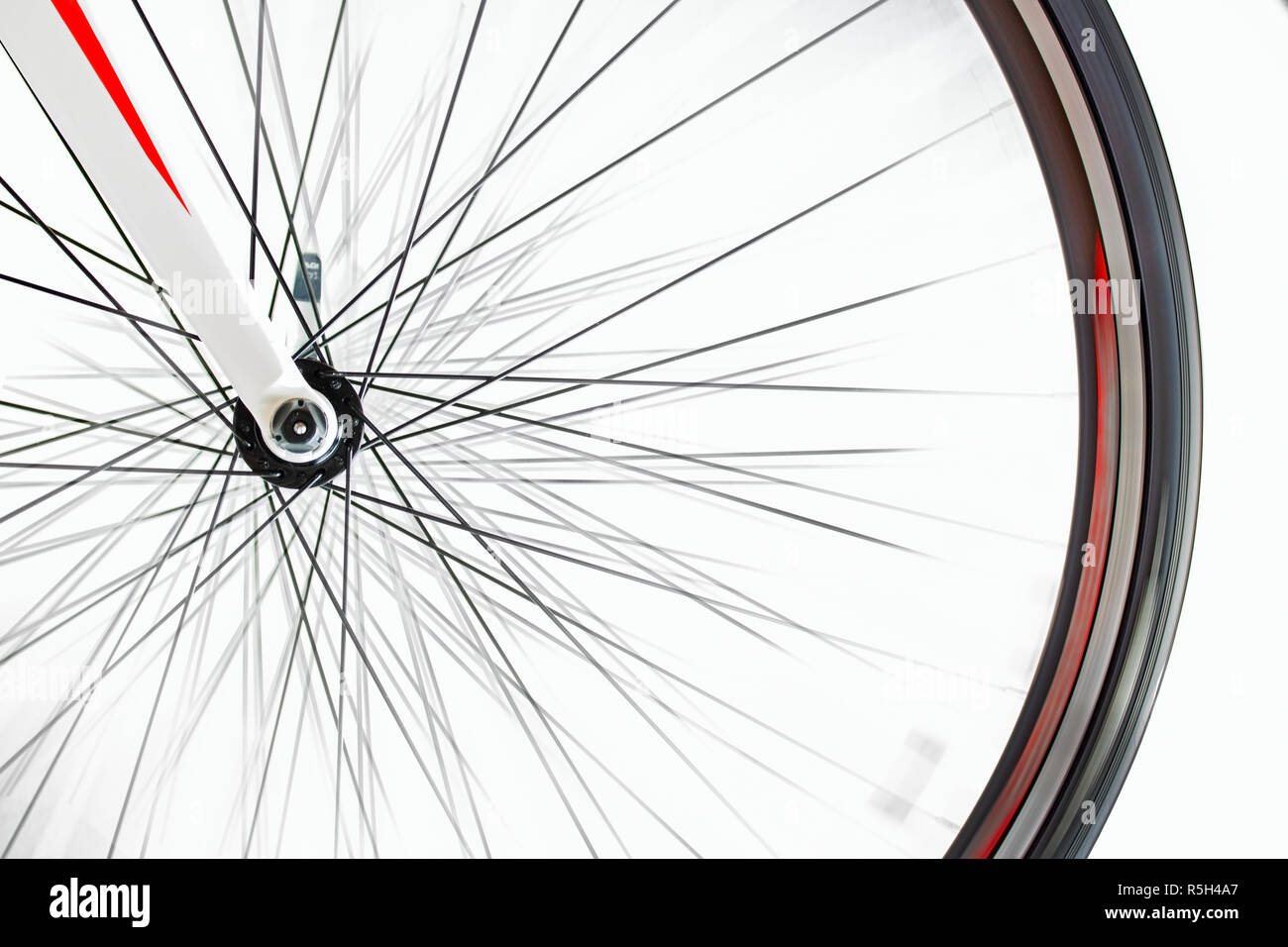 The front wheel of the bicycle rotates quickly on a white background. Detail of road bike while rotates. - Stock Image