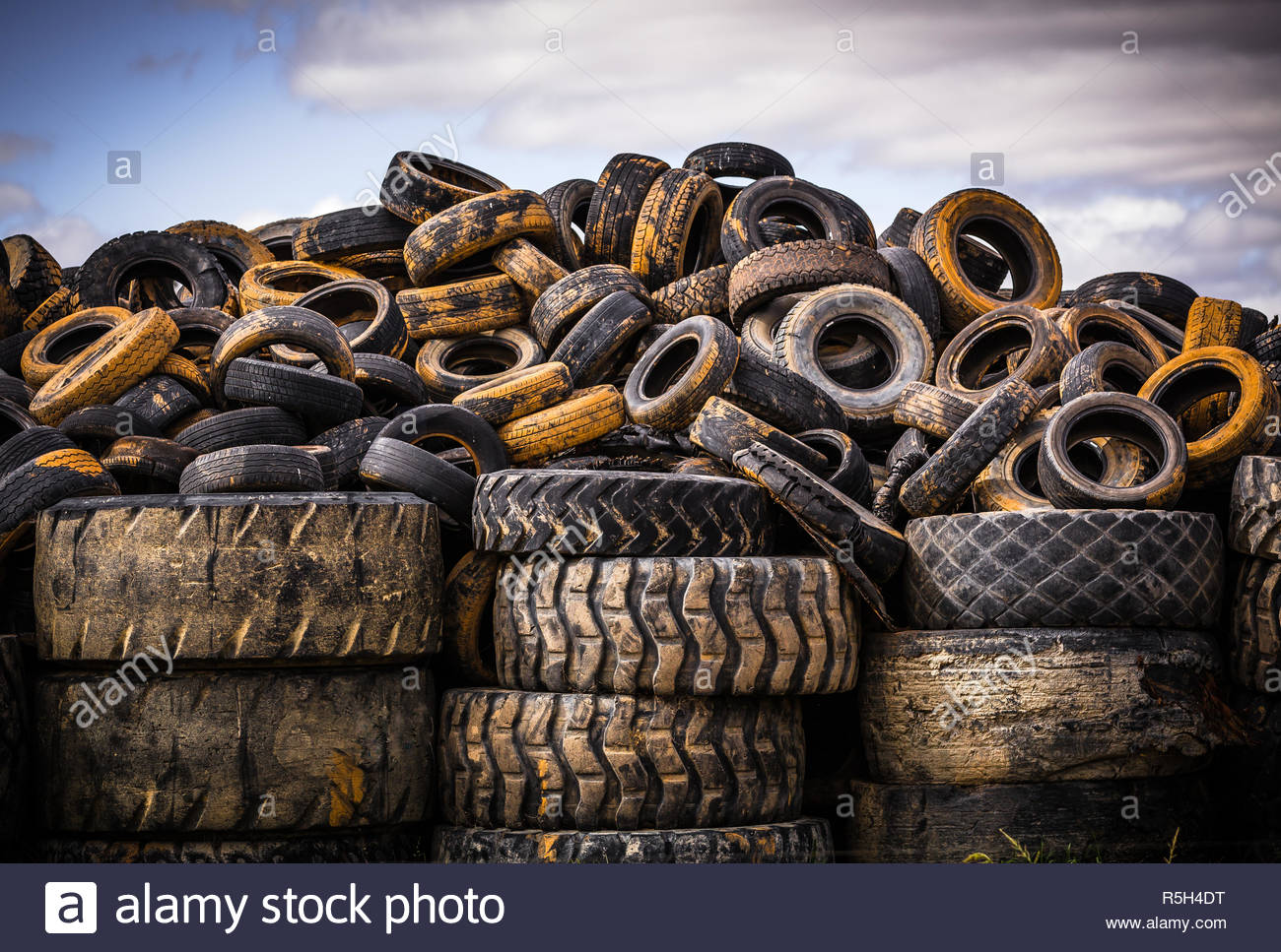 Pile of old used car and truck tires against an afternoon sky in Numurkah, Victoria. - Stock Image