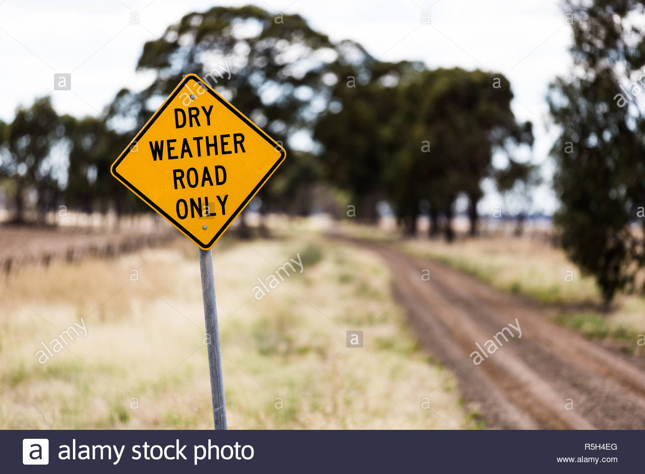 Dry weather only warning sign on a dirt road in rural Australia during drought conditions. - Stock Image