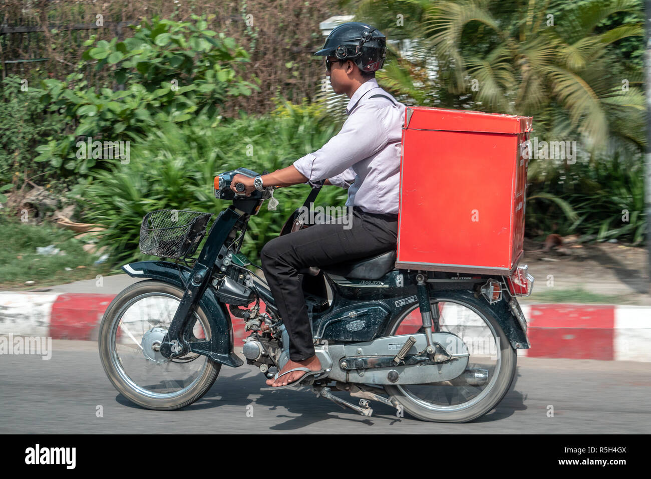 MANDALAY, MYANMAR, MAY 21 2018, Delivery of consignments on motorbike. Motorcyclist rides with delivery in the large red box on street, Burma. - Stock Image
