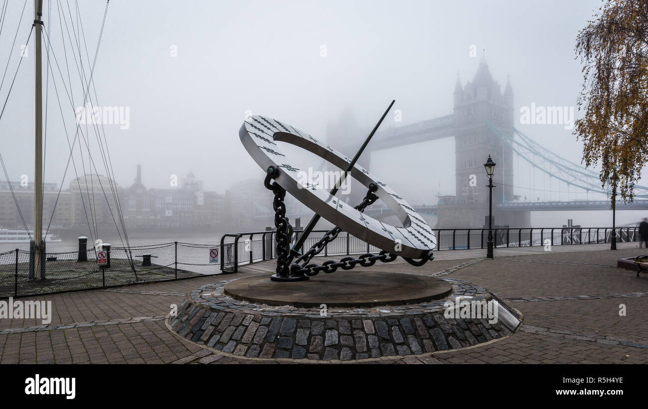 St Katharine's Dock Dial and Tower Bridge in the fog - Stock Image
