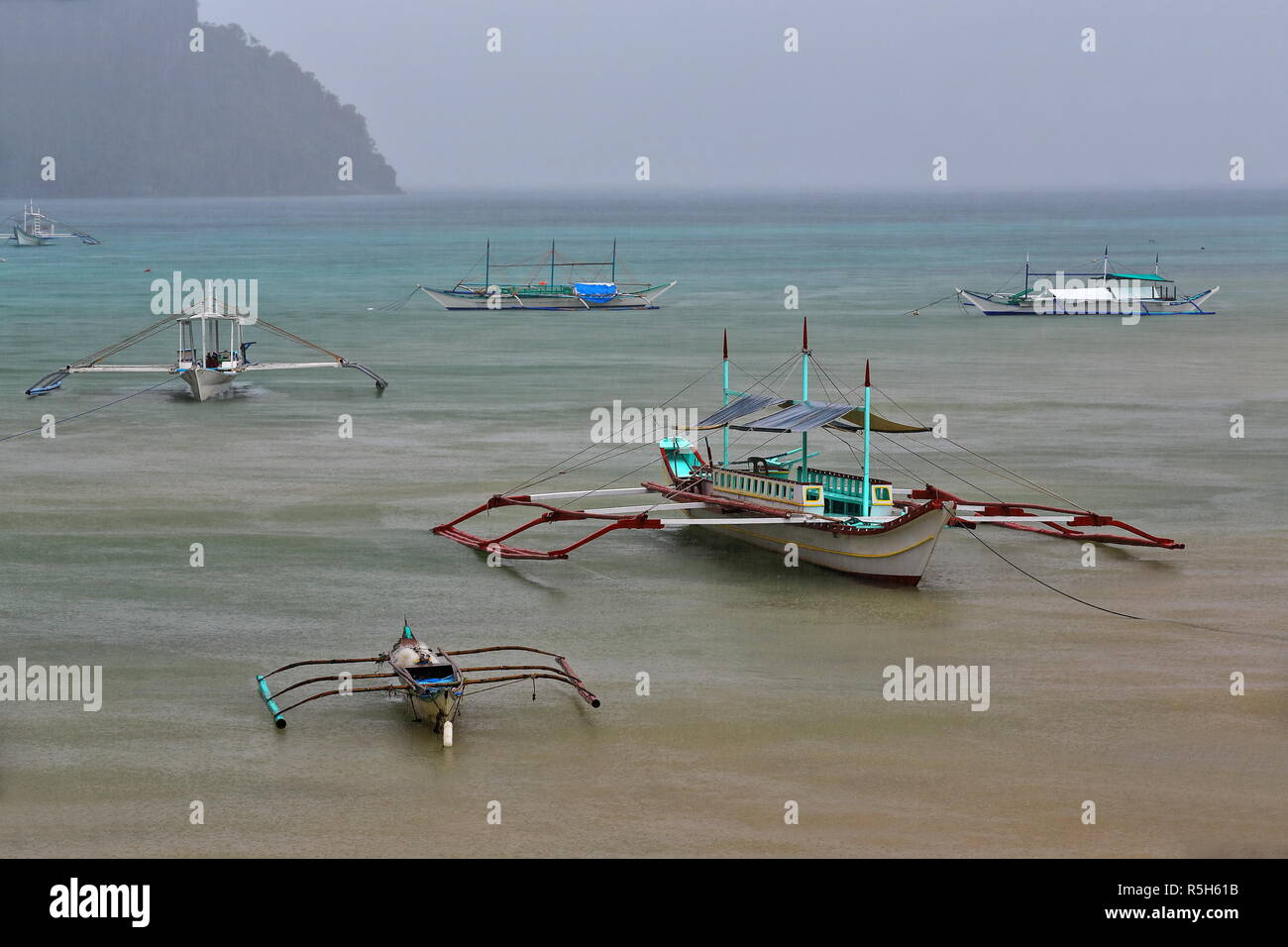 Fishing and tour boats stranded and moored at the beach under heavy rain preventing them from going out to sea to carry out their usual tasks-fishing  - Stock Image