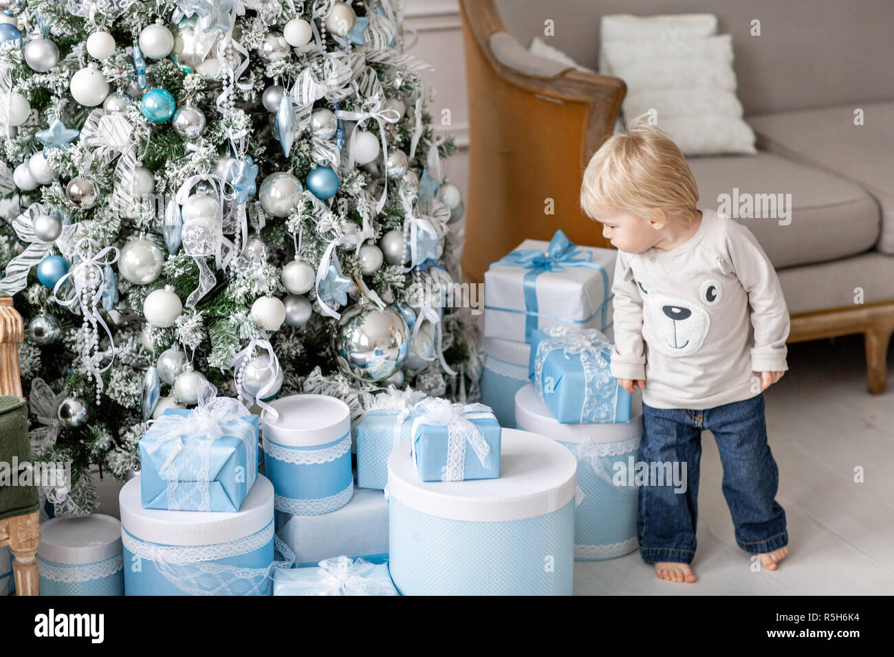 A Little Boy Stands Near A Lot Of Gifts Happy New Year Decorated