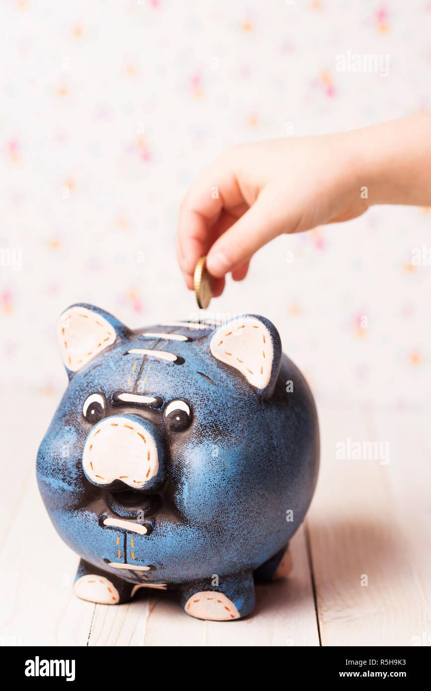 Little child depositing money into a piggy bank. - Stock Image