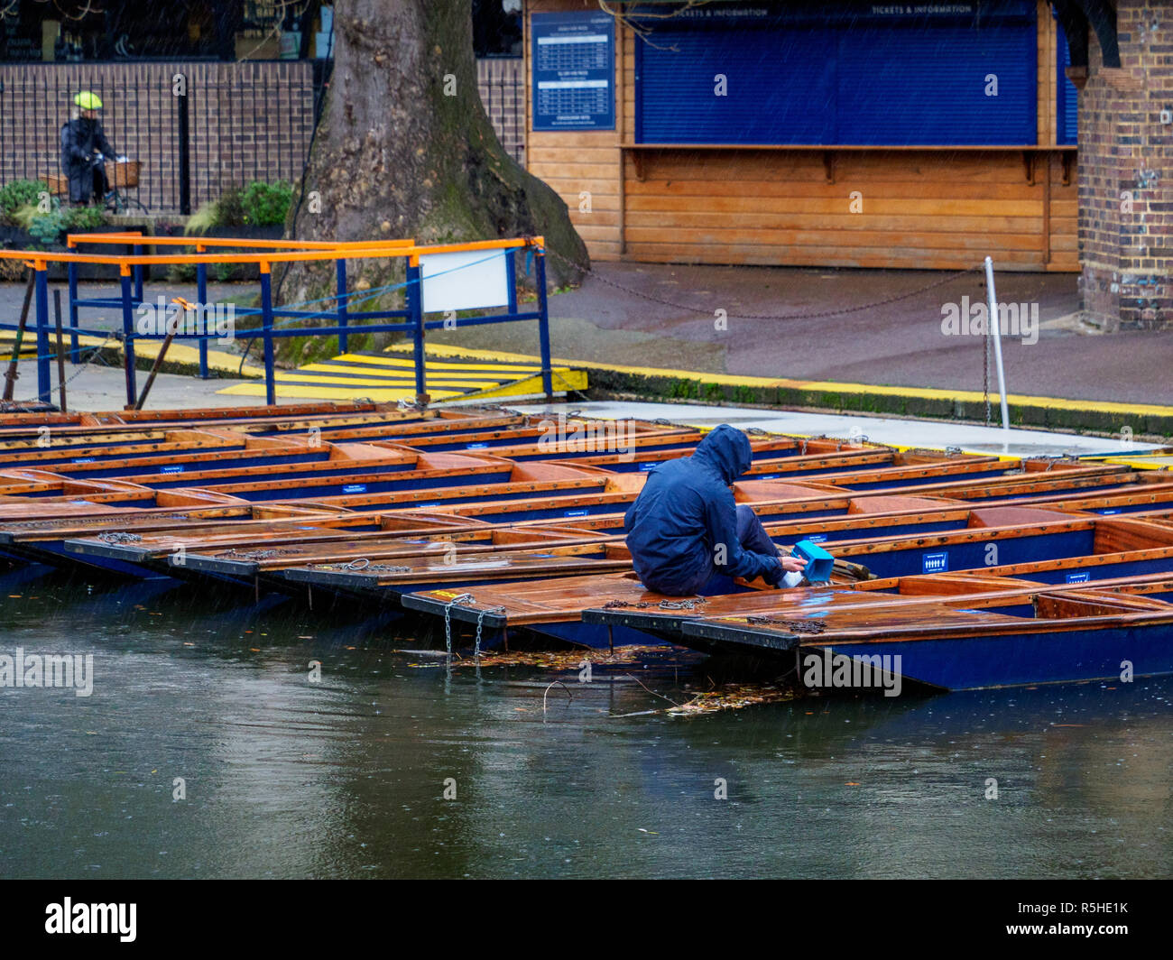 Winter Tourism Cambridge - an employee empties water from punts in Cambridge city centre - Stock Image