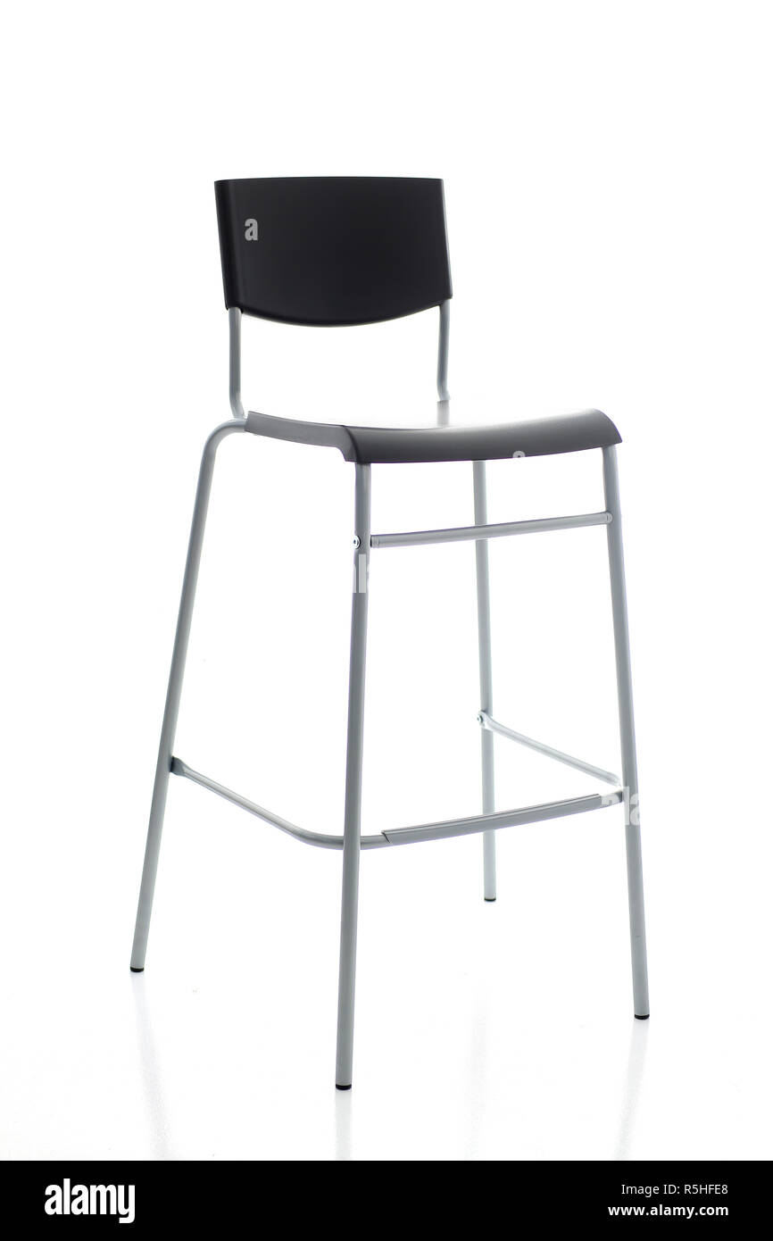Barstool on high metal legs with a black backboard - Stock Image