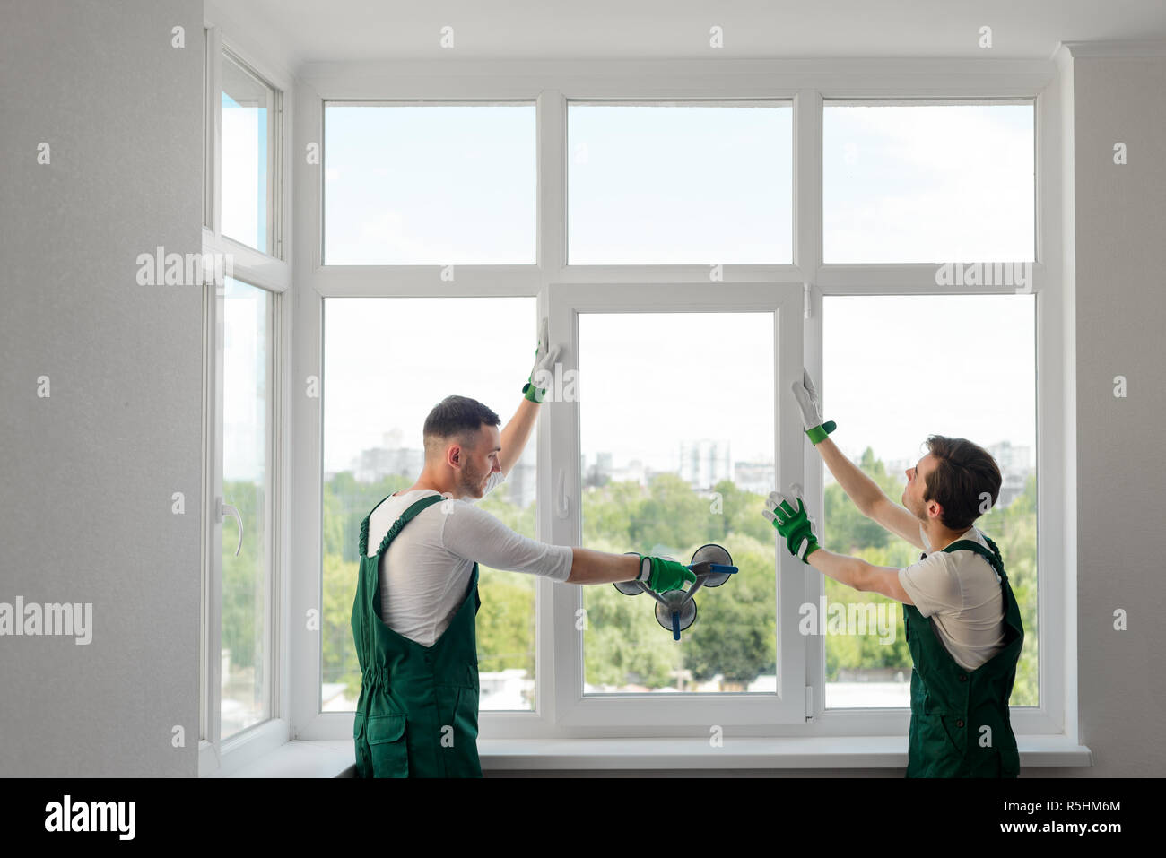 Construction workers install a window - Stock Image