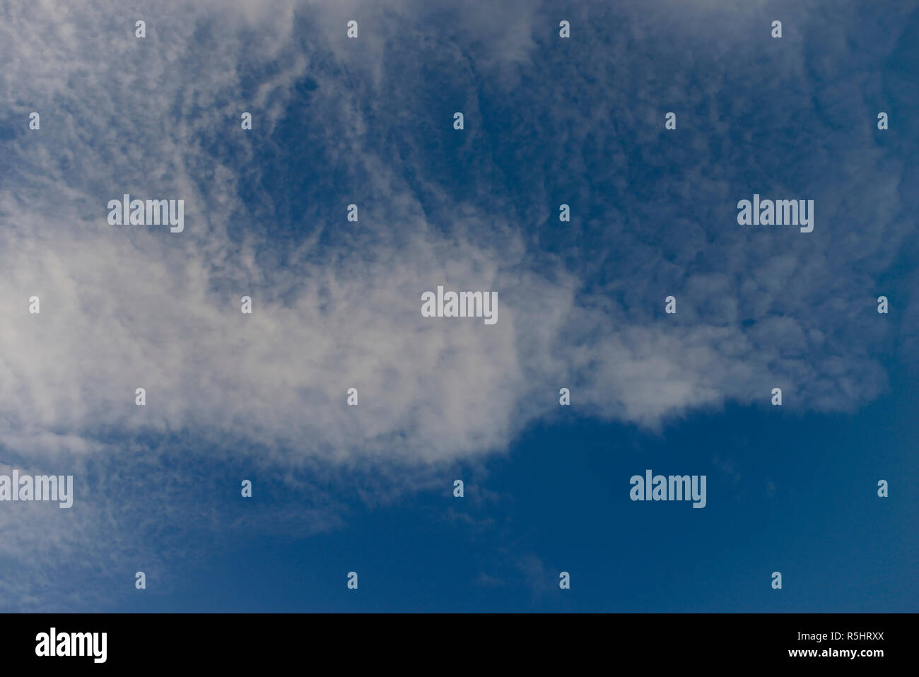 A layer of cirrus cloulds on blue sky - Stock Image