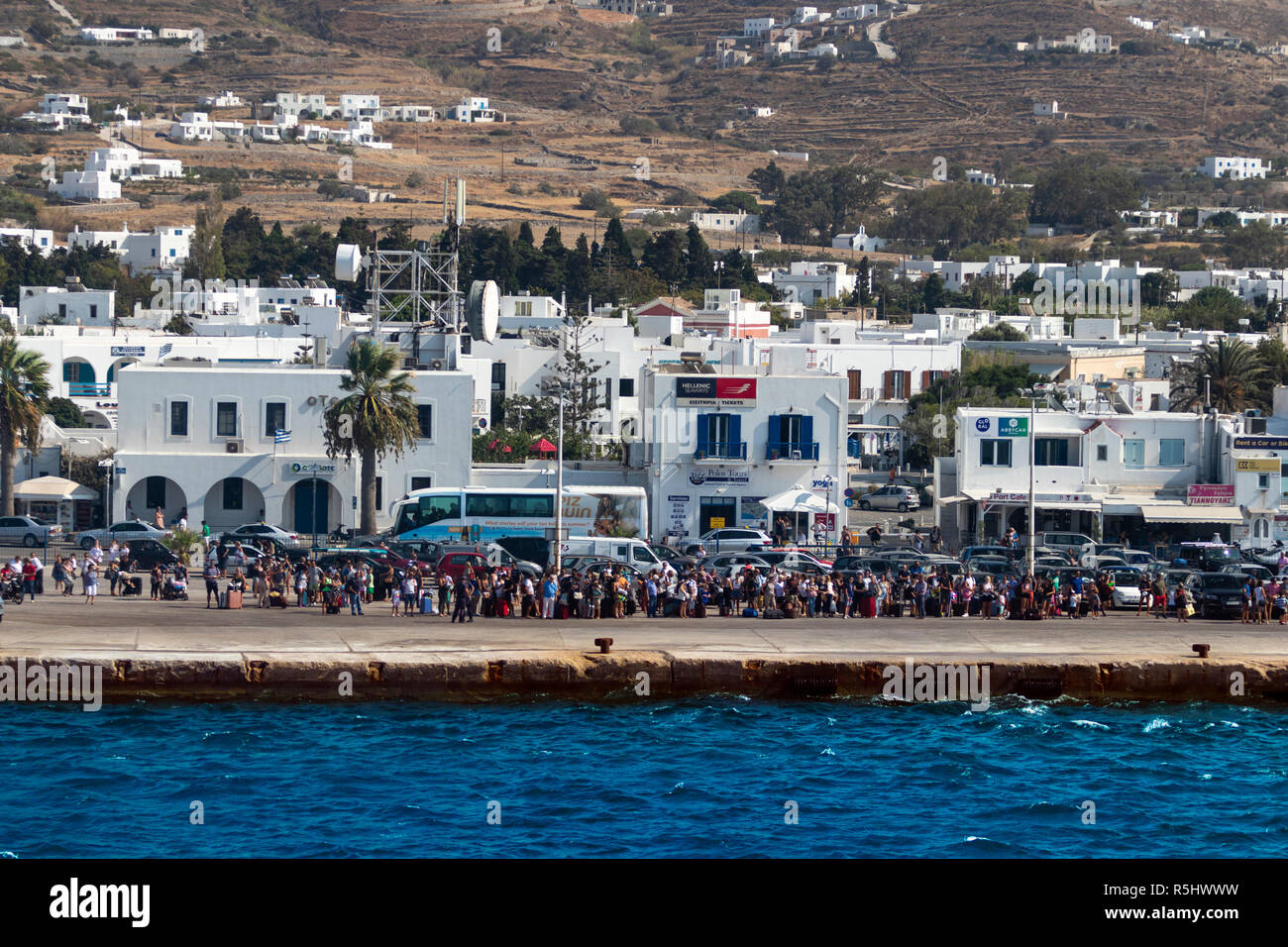 PAROS, GREECE - August 29, 2018: Crowd of tourists wait for embarkation at the ferry port of Paros island on a bright summer day. - Stock Image