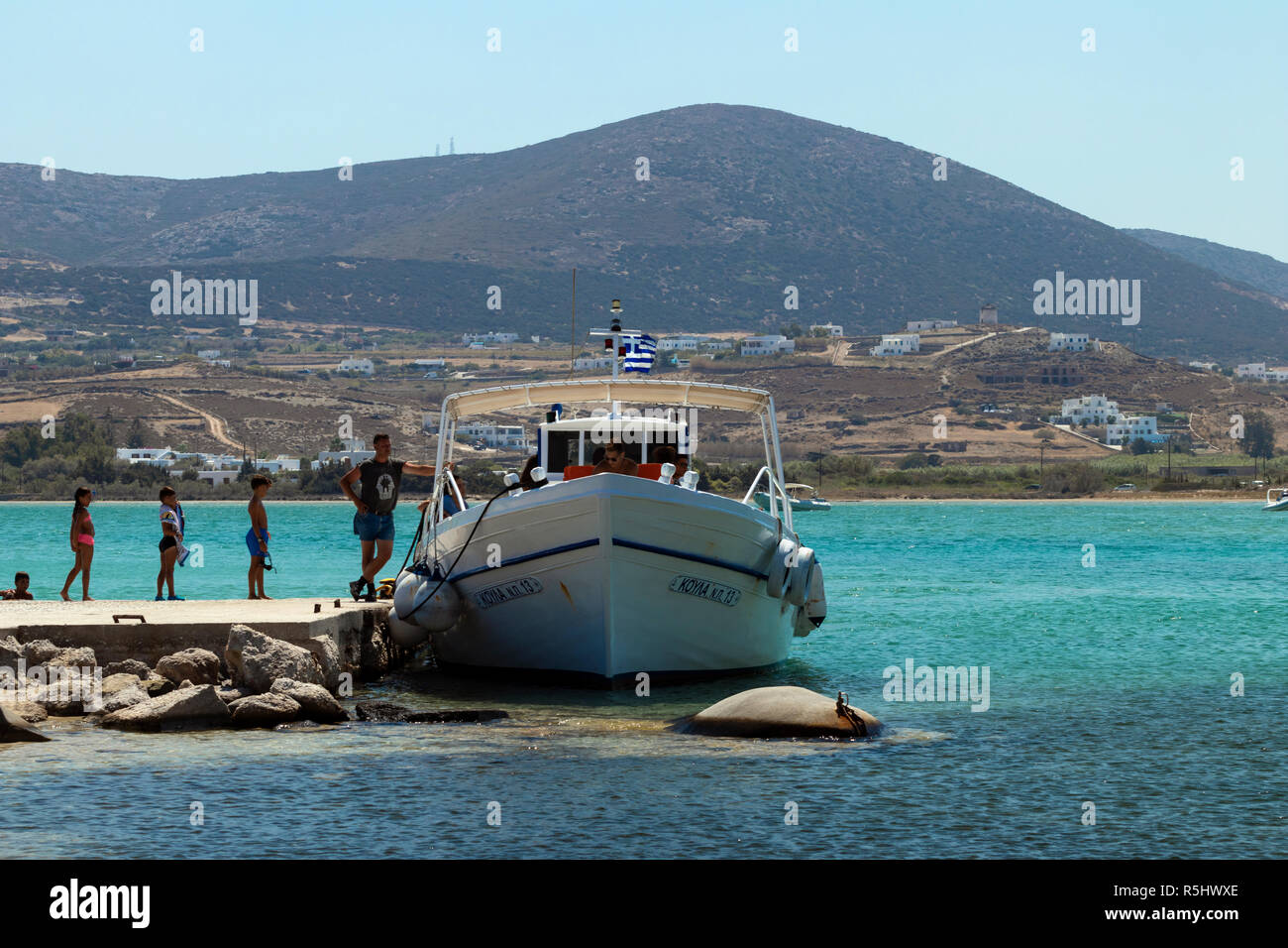 PAROS, GREECE - AUGUST 30, 2018: tourists are waiting to board a water taxi at an exclusive beach near Parikia on a hot sunny day. - Stock Image