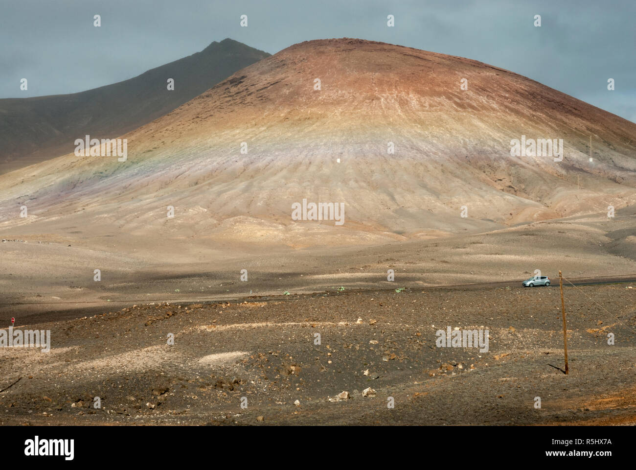 A view from a road en-route to Playa Blanca, Lanzarote, with a dramatic volcano swathed in multi coloured lava and pumice deposits. - Stock Image
