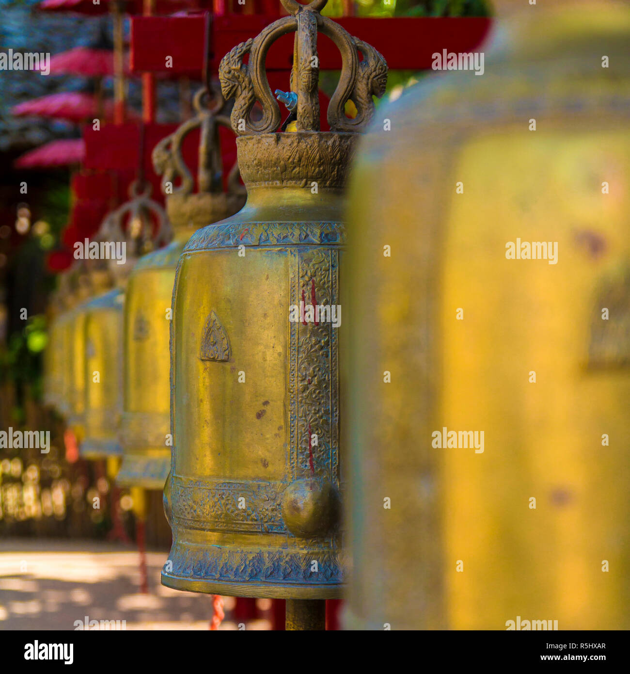 A long row of ritual brass bells in a Buddhist church in Chiang Mai Thailand. - Stock Image