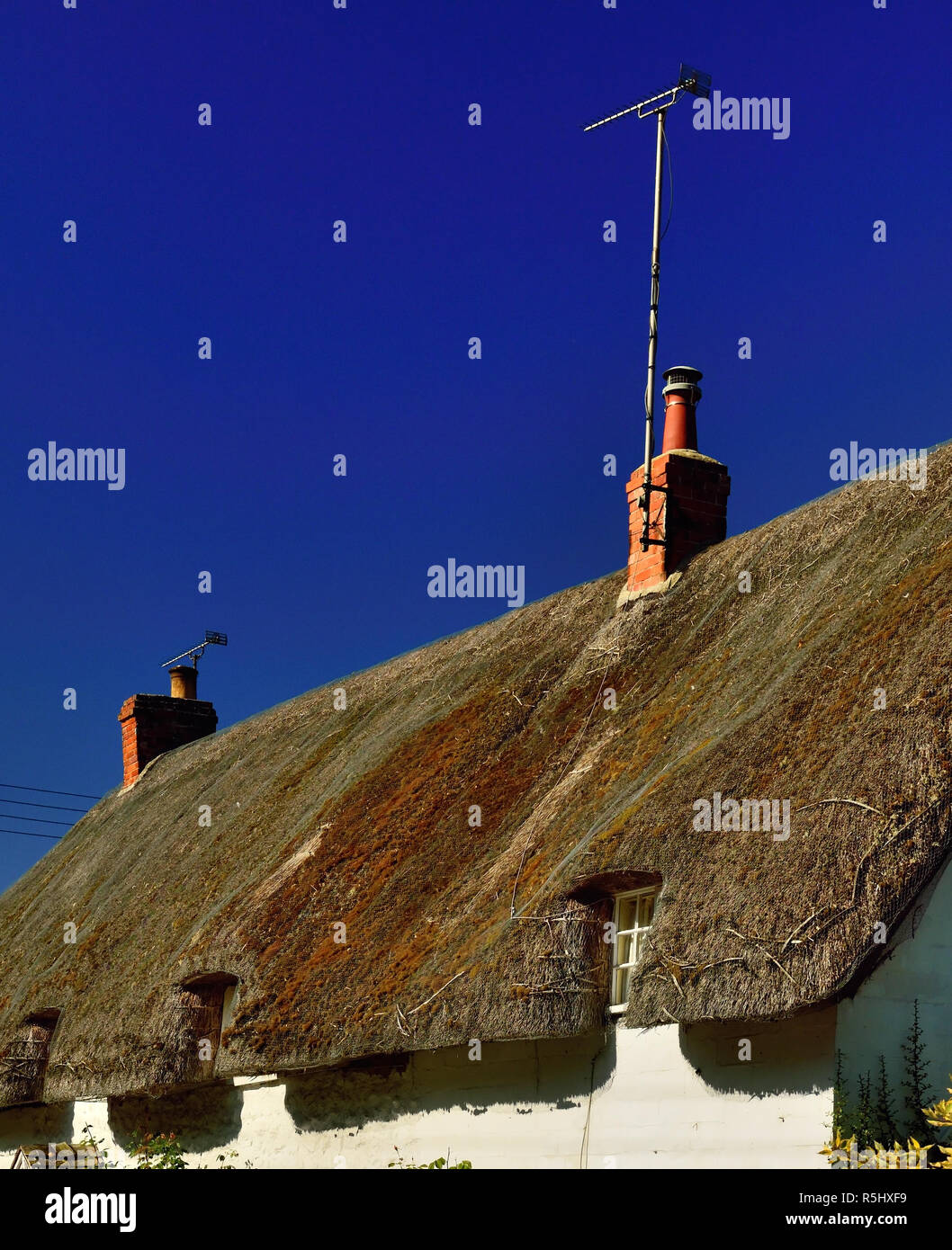 An old thatched cottage with a modern television aerial. - Stock Image