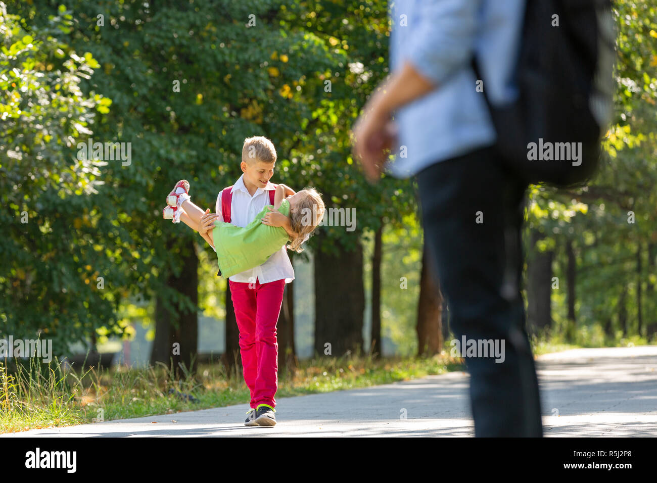 Happy laughing children playing and having fun in the park. Outdoors portrait on a sunny summer day. Older brother walking with younger sister in the park Stock Photo