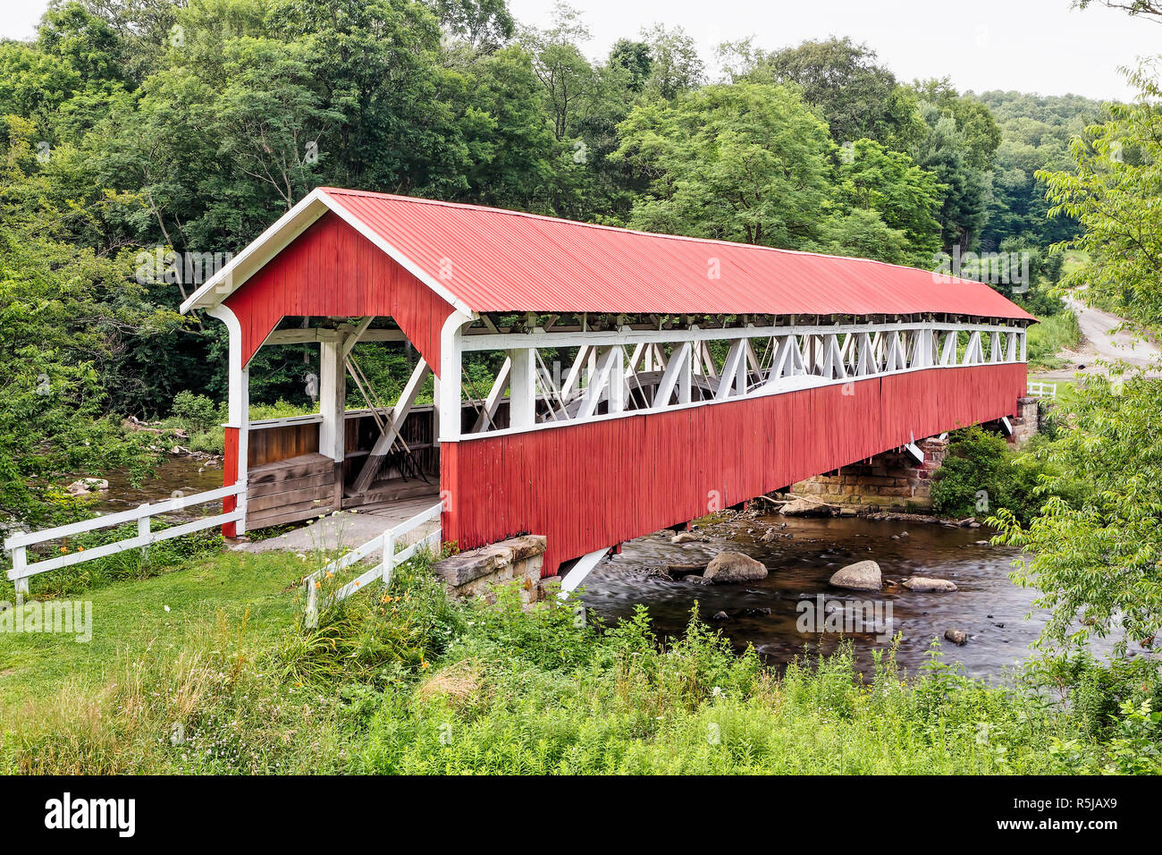 The historic red Barronvale Covered Bridge crosses Laurel Hill Creek in rural Somerset County, Pennsylvania. Stock Photo