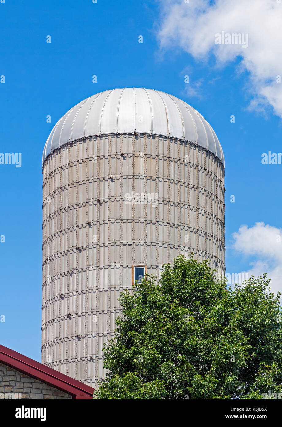 A silo tower stands against a cloudy blue sky on a Midwestern farm. Stock Photo