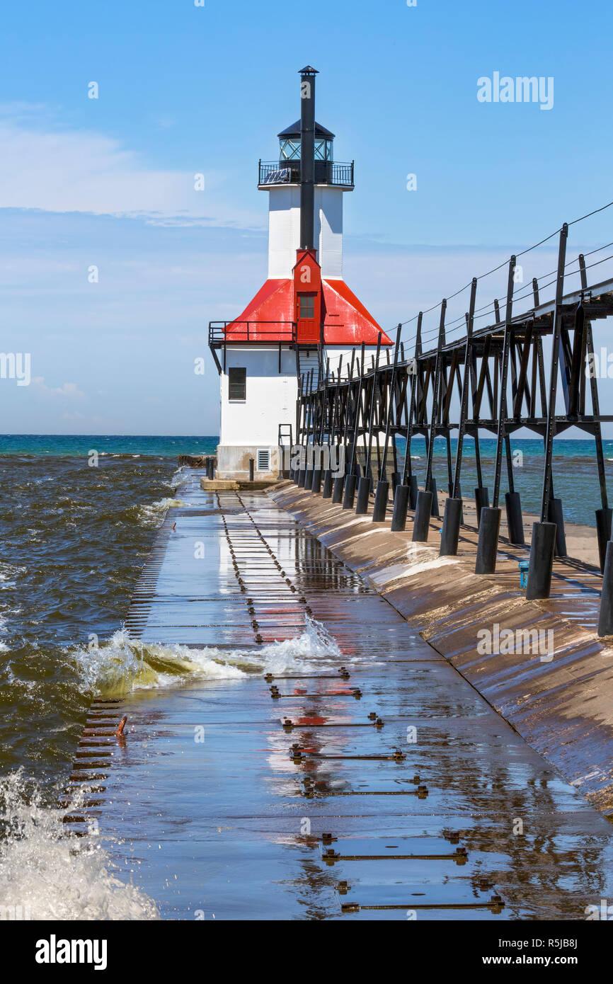 Lake Michigan waves splash over the breakwater at the St. Joseph, Michigan Lighthouse. Stock Photo