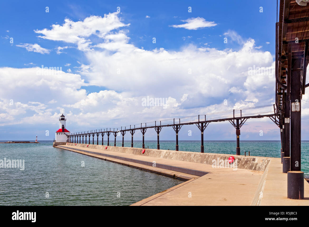 An elevated metal catwalk leads to the East Pierhead Lighthouse at Michigan City, Indiana on a partly cloudy summer afternoon. Stock Photo