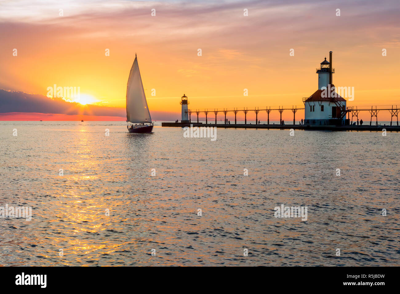 A sailboat rounds the breakwater near sunset on the longest day of the year by the Lighthouses at St. Joseph, Michigan with people fishing from and wa Stock Photo