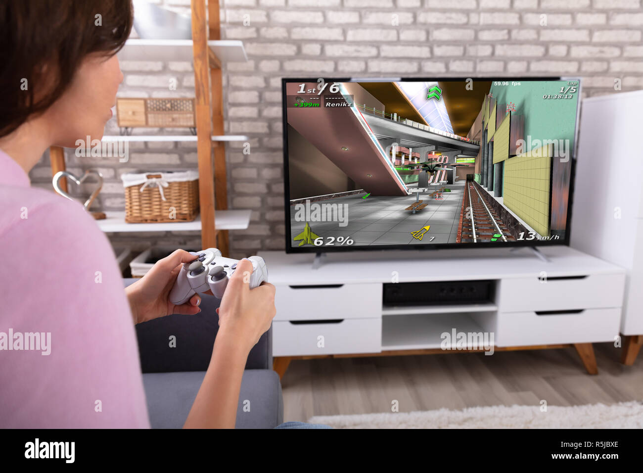 Woman Playing Video Game With Joystick On Television At Home Stock