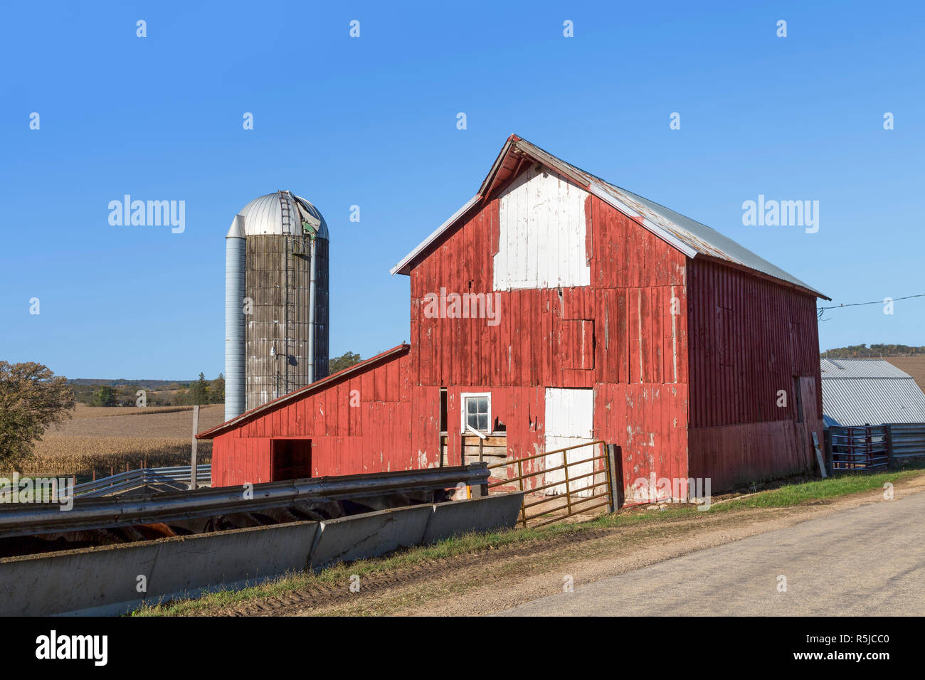 An old bright red barn and silo stand along the roadside on a rural Illinois farm. - Stock Image