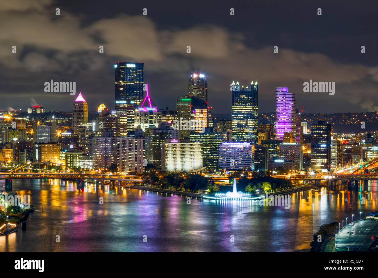 The city of Pittsburgh, Pennsylvania shines at night where the Allegheny and Monongahela Rivers meet to form the mighty Ohio. Stock Photo