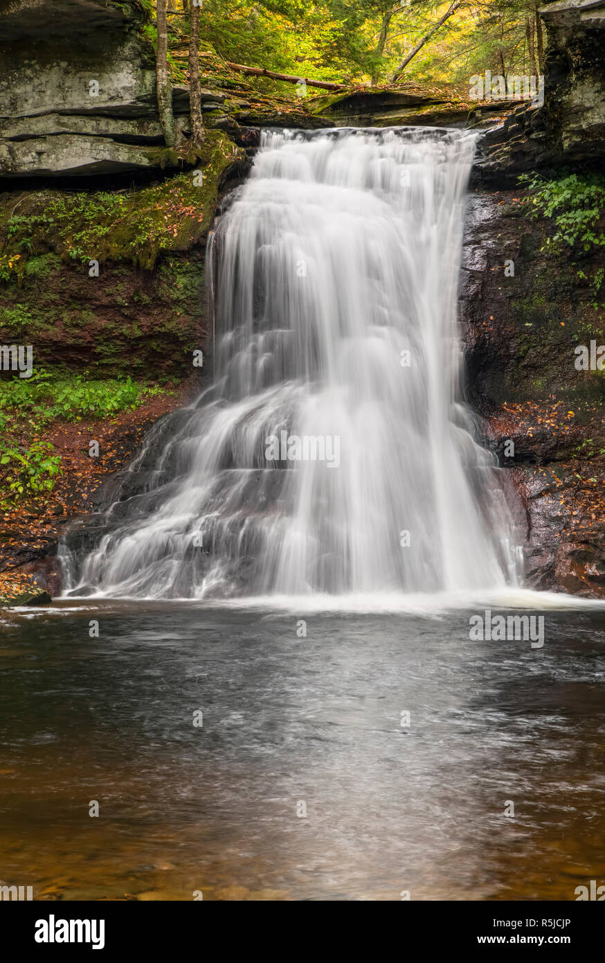 Sullivan Falls, a waterfall in northeastern Pennsylvania, plunges over a cliff surrounded by fall color. Stock Photo