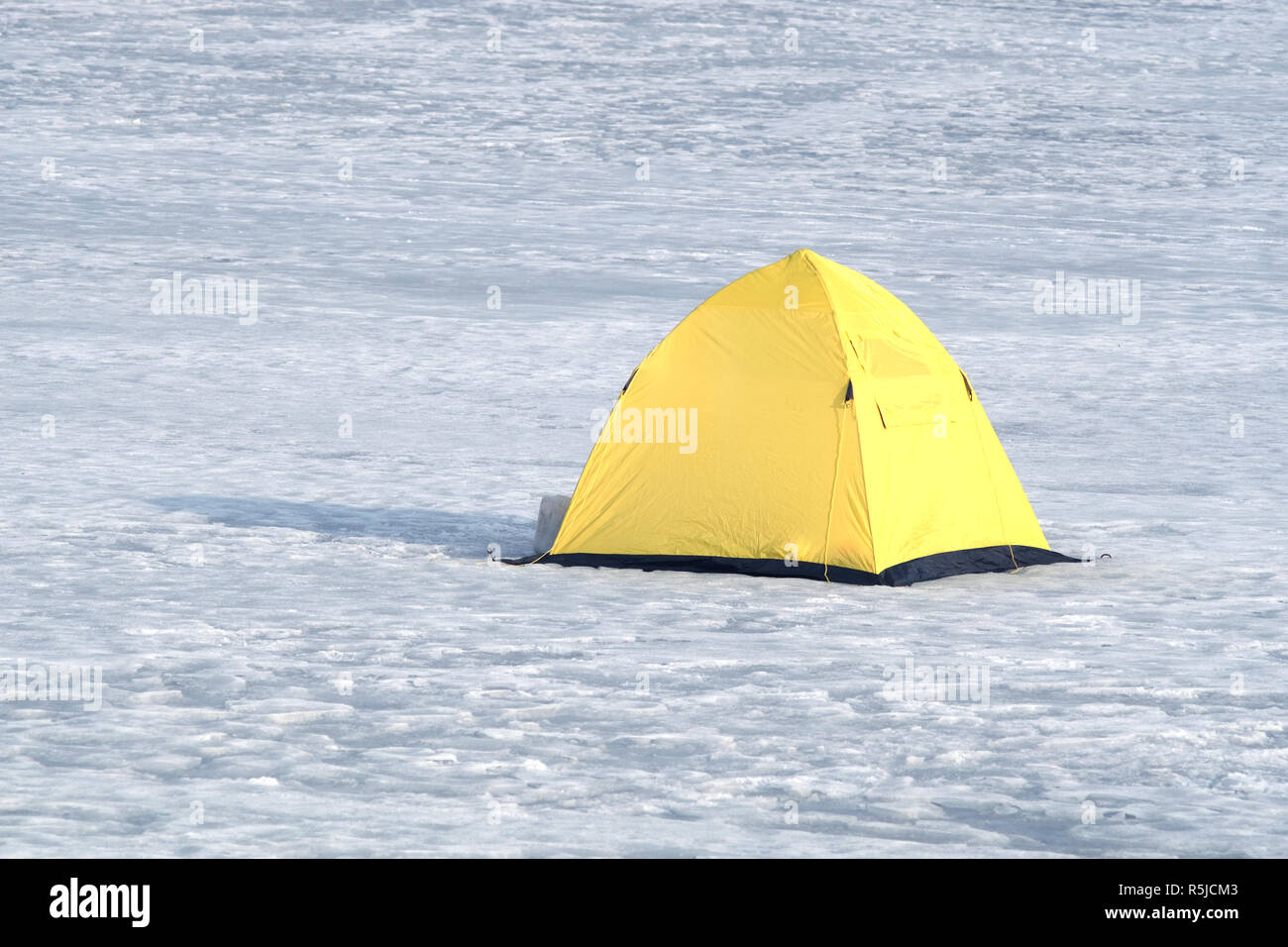 Winter fishing. Fisherman tent from yellow with black bottom in snow on frozen river in winter day closeup - Stock Image