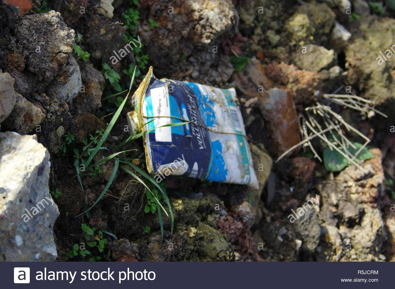 The forgotten garbage in the green meadow - Stock Image