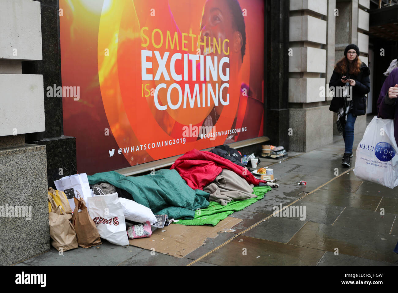Regents Street, London, UK1st Dec, 2018. A homeless person and belongings asleep, as people walk by and do their Christmas shopping. Penelope Barritt/Alamy Live News Stock Photo