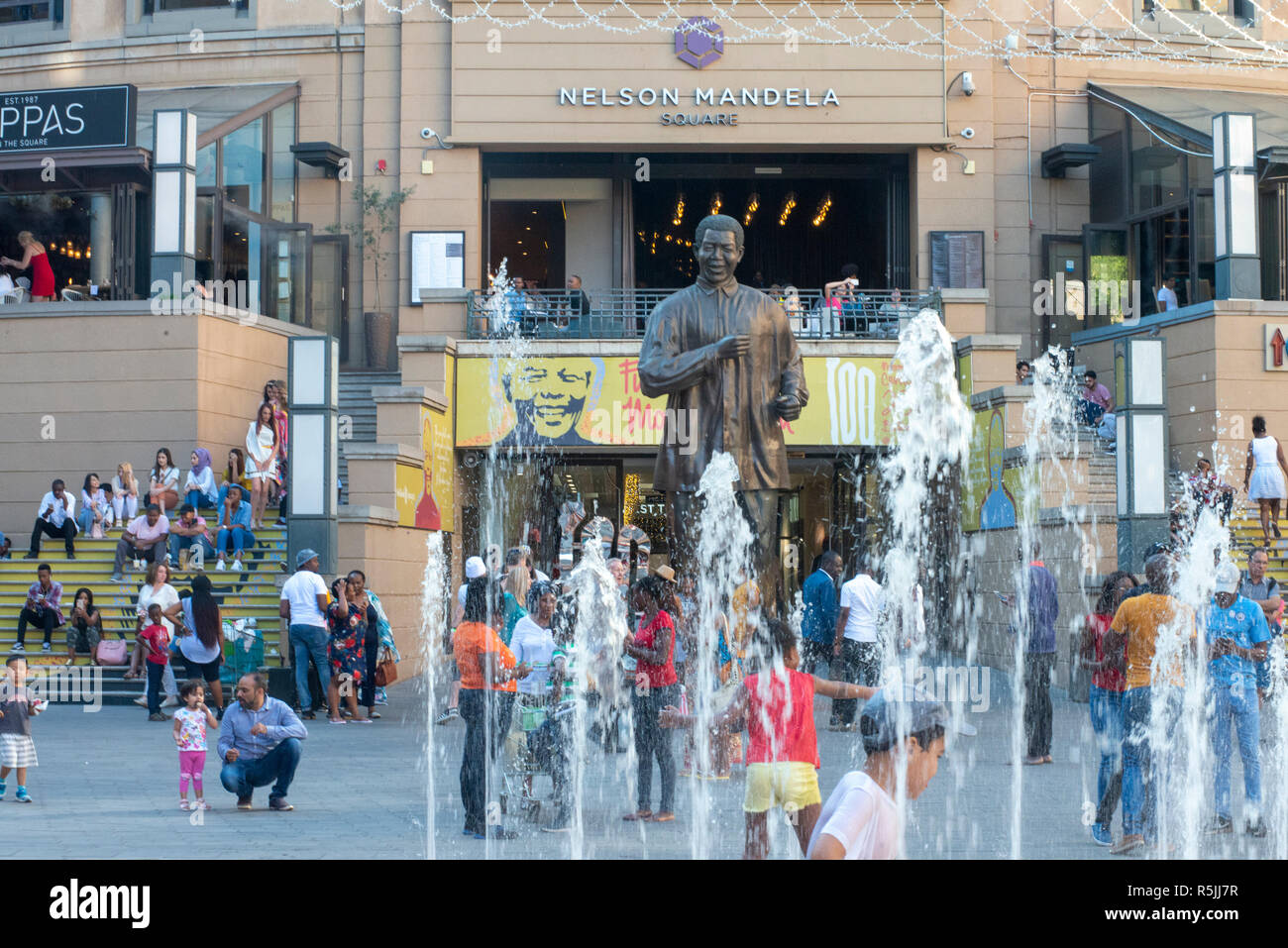 Johannesburg, South Africa, 1st December 2018. Children play in the fountain near the Nelson Mandela statue in Nelson Mandela Square in Sandton. South Africa is currently celebrating the centenary of Madiba's birth. Credit: Eva-Lotta Jansson/Alamy Live News Stock Photo