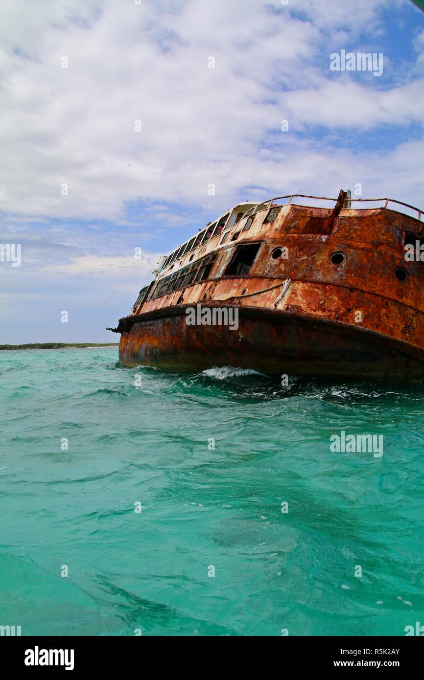 Rusted shipwreck on it's side in shallow Caribbean waters wrecked by a hurricane - Stock Image