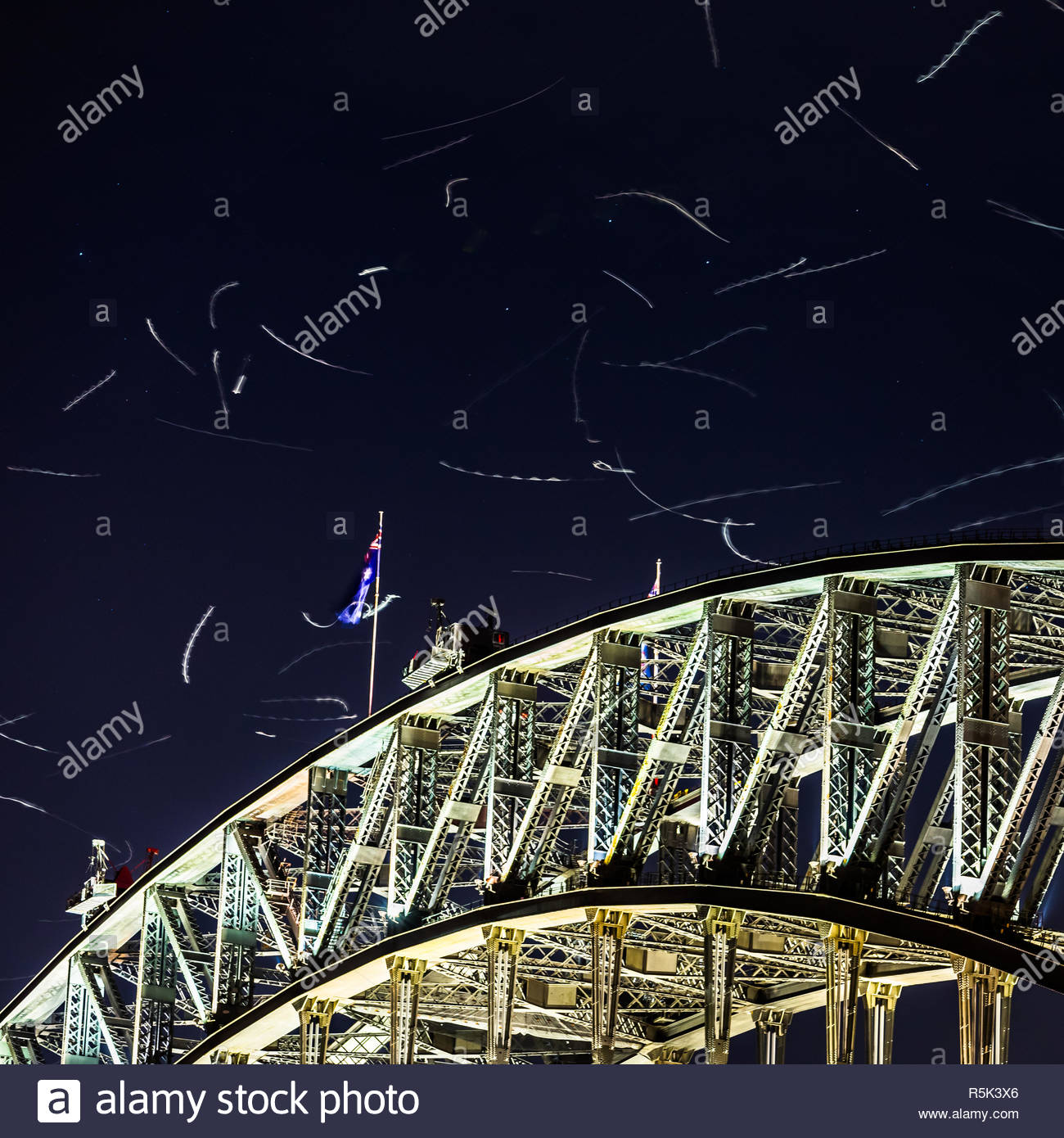 A long exposure records the movement of Silver Gulls as they dart above the Sydney Harbour Bridge, catching insects in the lights. - Stock Image