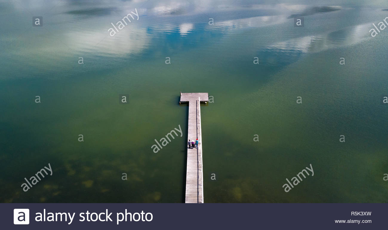 Drone aerial view from above of three people walking along a long wooden board jetty surrounded by a blue and green lake. - Stock Image