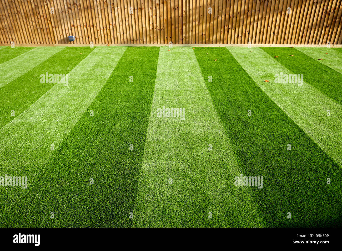 maintenance free artificial turf  lawn a modern synthetic grass carpet with stripes - Stock Image