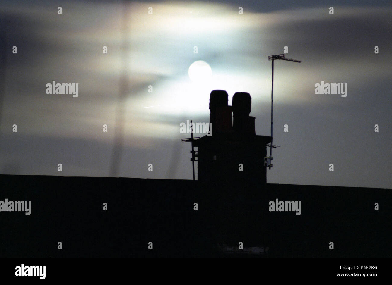 The moon over Clydebank, chimney tops and tv aerials. 1983 - Stock Image