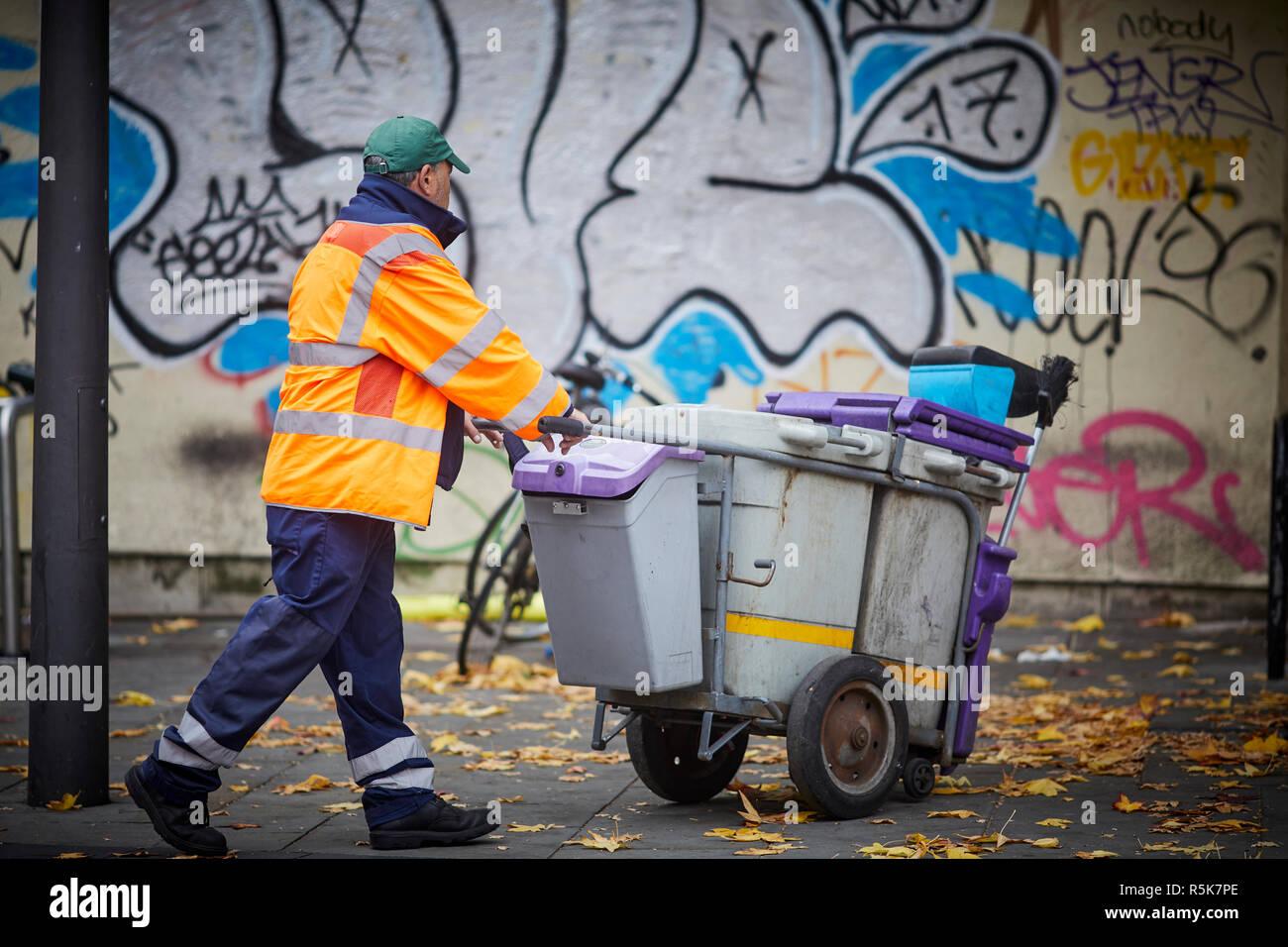 Liverpool city centre Bold Street littler picker pushing his bin cart past graffiti murals - Stock Image