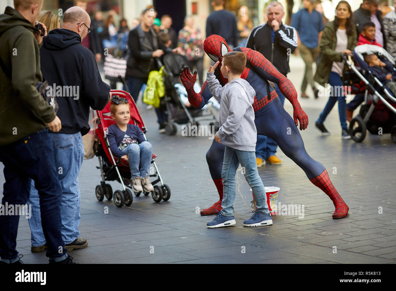 Liverpool city centre a busker dressed in costume as Spiderman - Stock Image