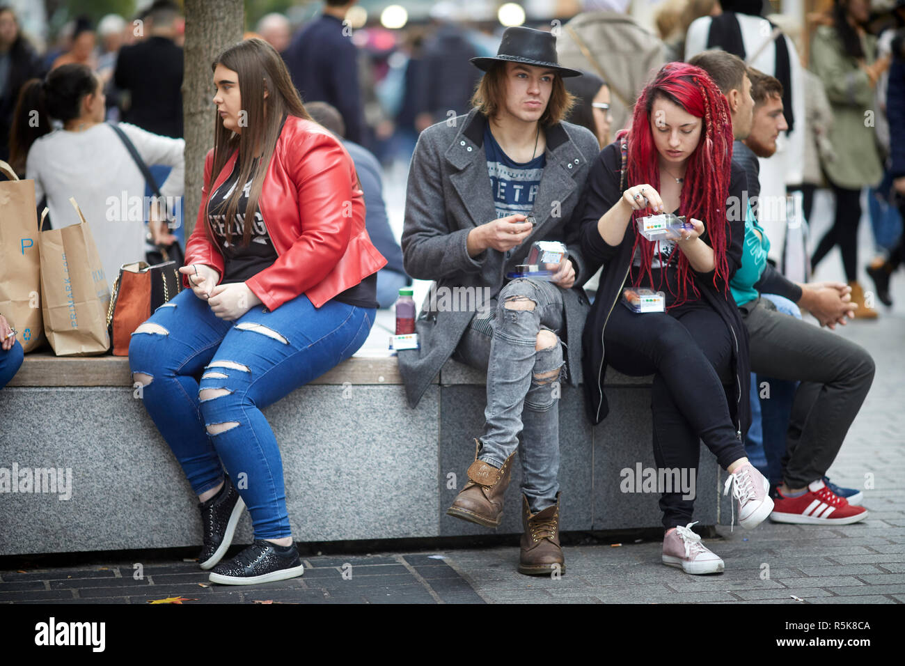 Liverpool city centre people resting on street furniture benches - Stock Image