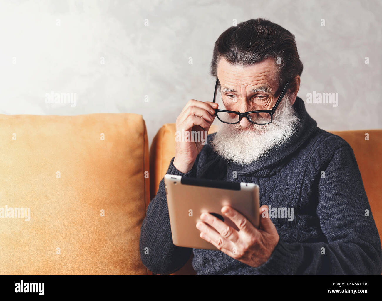 Clever senior bearded man in glasses wearing grey pullover reading electronic book on the digital tablet while sitting on a yellow sofa in his light living room, he looking over his glasses Stock Photo