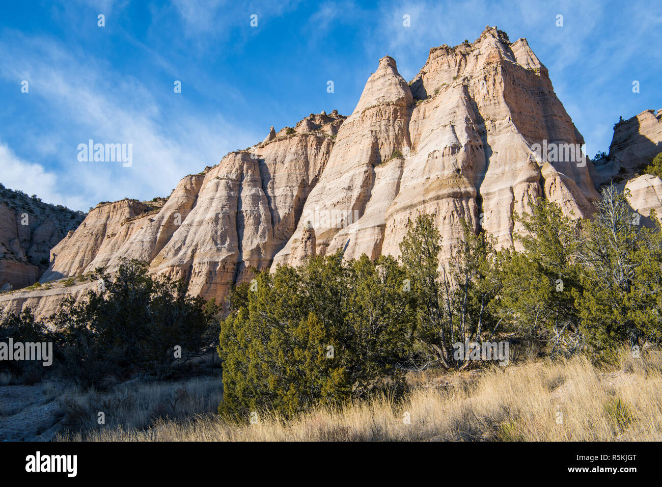 Steep, eroded rock formation with multiple sharp peaks under a blue sky with wispy clouds at Kasha-Katuwe Tent Rocks National Monument, New Mexico - Stock Image